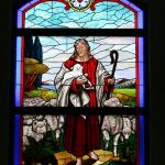 Stained glass window with Christ walking with sheep